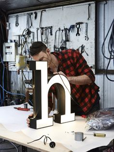 Melbourne lighting designer Daniel Giffin working on his 'H' light. Photo – Eve Wilson for The Design Files. Signage Board, Wayfinding Signage, Signage Design, Neon Lighting, Lighting Design, Custom Lighting, Lighting Ideas, Led Neon, Channel Letter Signs