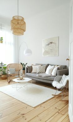 Bright and modern living room with a grey couch, a white rug and a light wooden floor. We love the Eames rocking chair, the woven pendant light and the curved floor lamp.