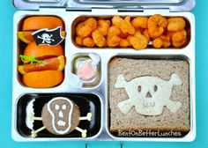 PlanetBox packed w' wedges o'oranges (t' prevent scurvy), barrrbeque Pirate's Booty, a Jolly Roger ham sandwich, a Jolly Roger carrot mini muffin, & a piece o' salt water taffy fer a treat