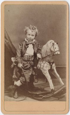 Finely dressed little boy with a rocking horse and riding crop, antique Victorian CDV photo, 1870s.