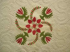Detail of coxcomb and currants/poinsettia applique, from past auction at Copake Auction