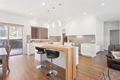 The natural beauty of Redheart Sassafrass timber shines through on this island servery, in a gleaming white kitchen.