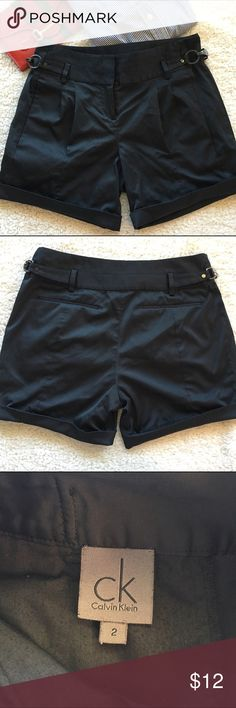 "Calvin Klein black satin shorts, size 2 Calvin Klein black shorts with front pleats, cuffed hem, buckle details in a thick material with a satiny sheen. Good used condition from a smoke-free/pet-free home. Inseam: 5"". Size: 2. Calvin Klein Shorts"