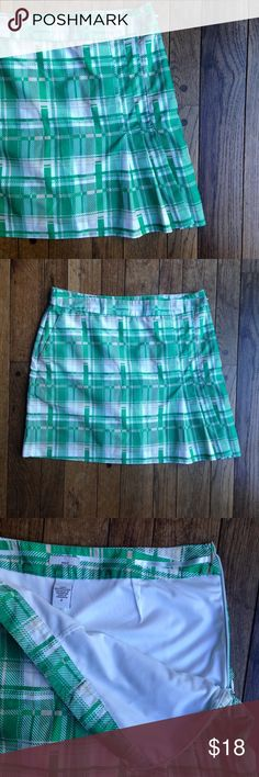 """Green plaid Izod golf skort EUC. 100% polyester. Green, tan and white plaid. Built in white shorts. Mesh pockets. Side zipper. Pleats on the bottom of one side. Sporty Chic!  Approximate measurements taken with garment laying flat: waist 30"""", hips 40"""", length 16"""". Izod Skirts Mini"""