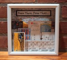 "Ticket Stub Shadow Box. I've seen many versions of this; here is my take on it. 8""-square shadow box from Michaels (actually a ""wish bank"" that has a nice size slot already cut in the top for additional tickets.) I used some map-print scrapbook paper and the phrase ""Been There, Done That...""."