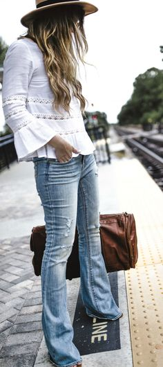 Boho fall transition look styled with peasant top, distress flared jeans, felt hat, and leather duffle bag