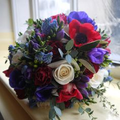Colourful, red, blue and cream spring flowers designed by Karen Woolven Floral Design Ltd www.kwfloraldesign.co.uk