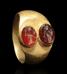 ROMAN GOLD RING WITH TWO OVAL CARNELIAN INTAGLIOS    One of Athena (Minerva), the virgin goddess of wisdom and the arts, and the other of Fortuna (Tyche), the goddess of good luck and destiny.    1st-2nd Century AD