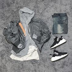 dark grey bomber. grey pullover hoodie. long tan tee. medium wash grey / blue denim. black / white sneakers.