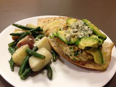 Grilled ground Chicken with peppers and parsley inside, topped with avocado and blue cheese on ciabatta. Along side cooked green beans and red potatoes in garlic
