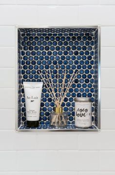 Chrome profiles provide a clean edge for the sapphire-colored penny round tiles that line the twin niches set into the guest quarters' tub-shower walls. TILE: Merola Tile. PROFILE EDGE: Schluter-Systems #bathroomideas #tiles