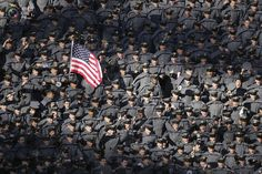 20 U.S. Military Academy cadets wave a flag in the stands prior to the 112th Army-Navy football game in Landover, Maryland, December 10, 2011.