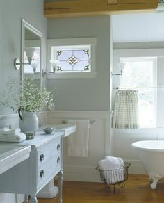 Awesome bathroom: wainscoting, claw-foot tub, hardwoods, pedestal sinks with an antique cabinet, and a stained glass window!