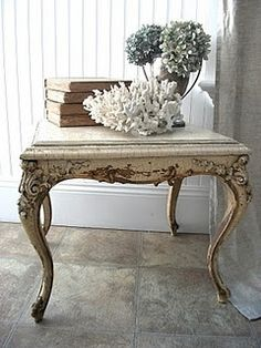 french table with ornate detail and crusty paint