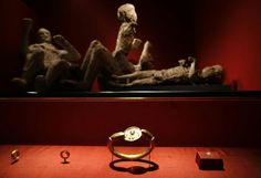 Jewelery found in the ruins of a house in Pompeii are displayed in front of a family of two adults and two children.