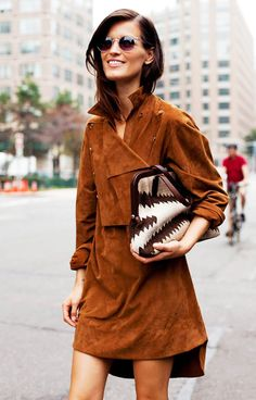 Hanneli Mustaparta wears a suede wrap dress, printed bag, and clear frame sunglasses
