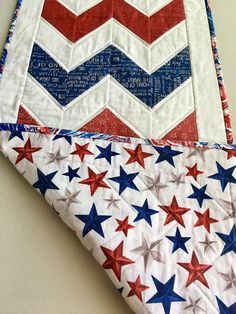 This is a hand made quilted table runner that measures 16 1/2 x 40 inches. It is made of 100% cotton featuring the patriotic colors of red, white and blue. The white fabric has white irregular circles on white. One of the reds and one of the blues has patriotic words, one blue has