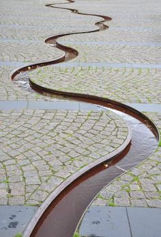 Rill curves thru cobblestone - PAM - meanderende afwateringsgoot - Public Square in Varde  |  Photo by Buelipix