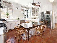 Saltillo tiled floors, traditional white cabinetry, a subway tile backsplash and glass front refrigerator.