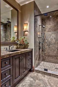 This bathroom features an all-over marble tile with a neutral color palette. The sink and shower areas share similar brushed metal fixtures, while the reflection in a mirror above the vanity shows a rainfall shower head at the opposite end of the glass-enclosed shower.