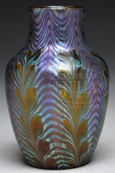 Loetz Phanomen Vase Has Blue Iridescent Waves Against A Gold Iridescent Background, With Blue Iridescence Having Very Strong Purple Highlights, Further Decorated With Gold Iridescent Stylized Leaves Extending Vertically Up The Body  -  James D. Julia, Inc. Auctioneers