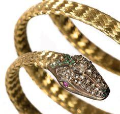 """Bracelet """"serpent"""" en or jaune 18K (750°/00), la tête de forme losangique sertie de diamants de taille ancienne roses et poires, de cabochons de rubis pour les yeux et de pierres vertes, est accolée au… - Tessier & Sarrou - 22/06/2016"""