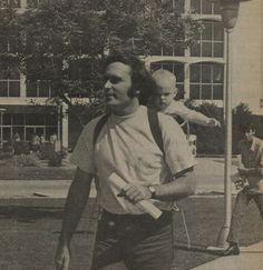 Photograph of Greg French and his 7-month-old son, Michael, walking to class together. The image ran in the Daily Sundial, the campus newspaper of San Fernando Valley State College (now CSUN), November 17, 1971. The building behind the pair is the former Administration building, now known as Bayramian Hall. Journalism Department Records.