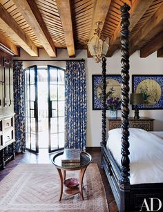 In a guest room, the house's blue-and-white motif continues with curtains made of a Kravet fabric and, on the adjacent wall, two antique ceiling panels from a Japanese temple.