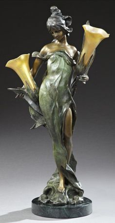 After Pierre Roche (1855-1922), Art Nouveau Style PATINATED BRONZE FIGURAL LAMP, OF A FEMALE CENTERING FLOWERS, WITH TWO GOLD IRIDECENT FLORIFORM ART GLASS SHADES, ON A CIRCULAR VERDE ANTICO MARBLE BASE