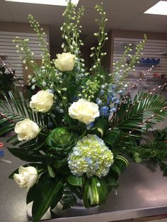 Blue hydrangea, blue delphiniums, white roses, kale & pussy willow with unique greenery by Donna Jeffries