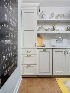 Stunning kitchen features gray walls which highlight a large vintage subway sign alongside light gray cabinets adorned with brushed nickel pulls and Statuary Marble Counters topped with a Kohler Gilford Sink framed by a subway tiled backsplash and floating shelves with led lights.