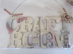 Decoupage craft room sign with floral embellishment and ribbon.