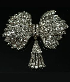 A Georgian diamond bow brooch, English, 1820s. Cushion-shaped diamonds, rose-cut diamonds, silver and gold.