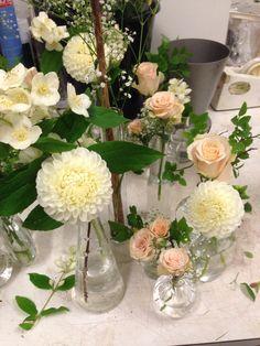 Borddekorasjon til bryllup av roser, jasmin, blåbærblader, dahlia og brudeslør