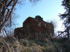 This abandoned old brick farmhouse sits vacant with a collapsed roof north of Sutliff, IA.