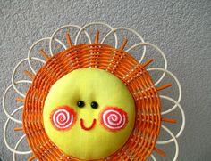 Sluníčko oranžové s bílým okrajem Usměvavá dekorace do dětského pokoje, na dveře, do okna. Sluníčko je upletené z pedigu o průměru 23 cm. Obličej je z bavlny. Očka a úsměv je z korálků. Lze zavěsit za poutko nebo za paprsky.