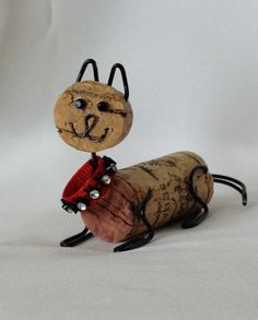 This is a one of a kind Fe-Wine cork art cat. It is made with an upcycled cork and other new materials. Each one has a personality and features a rhinestone collar. They are easy to use standing alone or hanging from the tree or even tied on a gift.