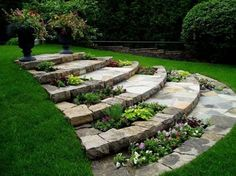 Clever use of beautiful stone for steps with inset flowerbeds in this backyard