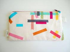 I really like this. If you just buy a plain canvas pencil case, and randomly stick a bunch of brightly coloured washi tape on it, it looks so rad.