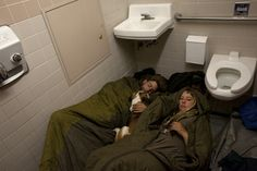 Micaela, Nathan and their dog, Mung, fall asleep in a rest stop bathroom on a rainy night. Kitra Cahana, Washington, 2011.