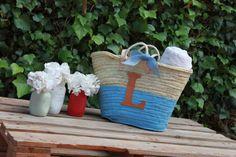Cesto de mimbre pintado y personalizado con inicial en cuero y lazo de saco a juego. www.lepetitatelierbcn.com