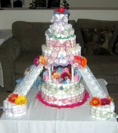 6 Tier Diaper Cake with stairs & two - 1 Tier Diaper Cakes. Centerpiece designed using baby accessories [BABY box letters, strollers, plastic babies, etc.) and flowers for decoration. Each tier wrapped with floral ribbons in multiple colors to secure diapers together.