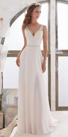 Simply and Elegant, This Georgette Sheath Gown Features an Embroidered Bodice with Illusion Side Insets and Crystal Beaded Trim. Deep V Neckline and Back.