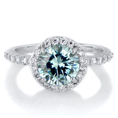 Silvertone December Imitation Birthstone Ring - Blue CZ. Celebrate life with a Sterling Silver Imitation Birthstone Ring!. Imitation Birthstone rings are the perfect way to gift someone something special on their birthday. This December blue CZ ring features a 2 carat round cut stone that is surrounded by petite size clear stones giving off the angelic halo effect. Smaller size CZs extend partially down each side of the band for even more radiance. Sparkle in style during your birth month…