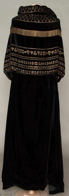 velvet & lame evening cape, c. 1915 Black silk velvet long cape, blouson top w/ rows of gold lame hieroglyphics, at back sides 2 black silk tasseled cords to either tie in front or hang down back, black silk charmeuse lining