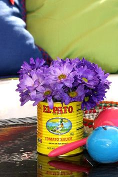 Another cute fiesta theme table decor... flowers in Spanish cans! So easy and cheap.. With tissue flowers..