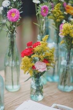 sweet floral arrangements in aqua bottles, photo from By the Robinsons http://ruffledblog.com/sunken-gardens-florida-wedding #flowers #centerpieces