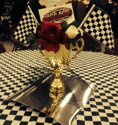 Racing Theme Trophy Cup Centerpiece.                                 (Made by original pinner) #racing #nascar Trophy cups as the base of the arrangement were purchased from an awards and trophy type store, filled w styrofoam and finished with artificial flowers, track logo and small checkered flags. *update* I recently saw similar trophy cups @ party city for a much lower price!