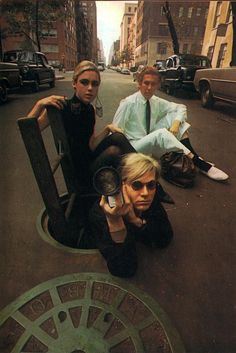 Andy Warhol and Edie Sedgwick (Chuck Klein sitting there in the background) teetering over a New York CIty manhole.
