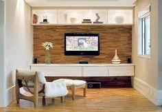 A madeira em tom médio não atrapalha a imagem da TV e o móvel parece flutuar a 35 cm do piso. No alto, a estante tem nichos para peças decorativas e spots com lâmpadas dicroicas para iluminação indireta